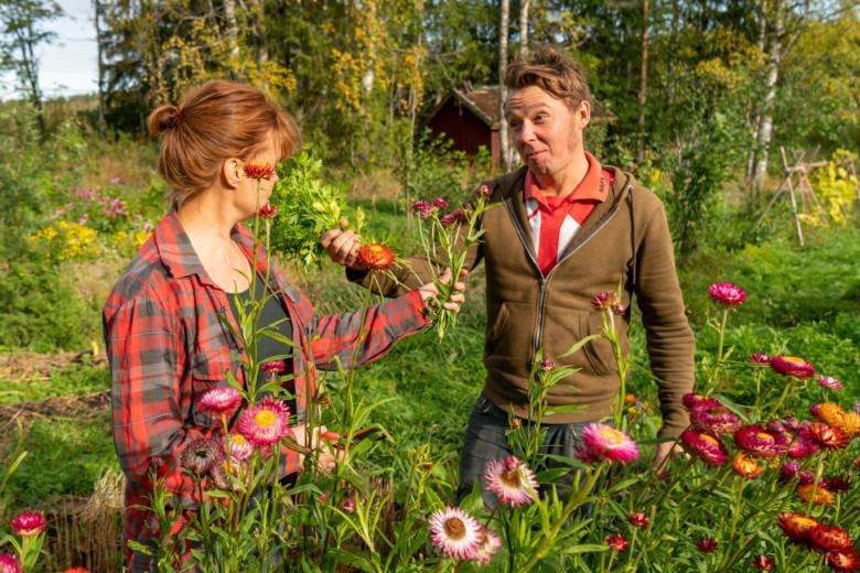 Pia ja Glenn haistelevat toistensa yrtti- ja kukkakimppuja.