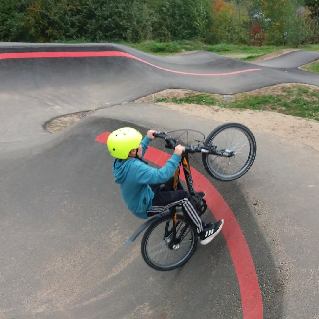 Poika hyppää pyörällä pumptrack-radalla.