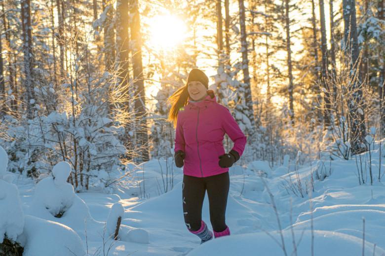 Nainen juoksee lumisessa metsässä villasukilla.