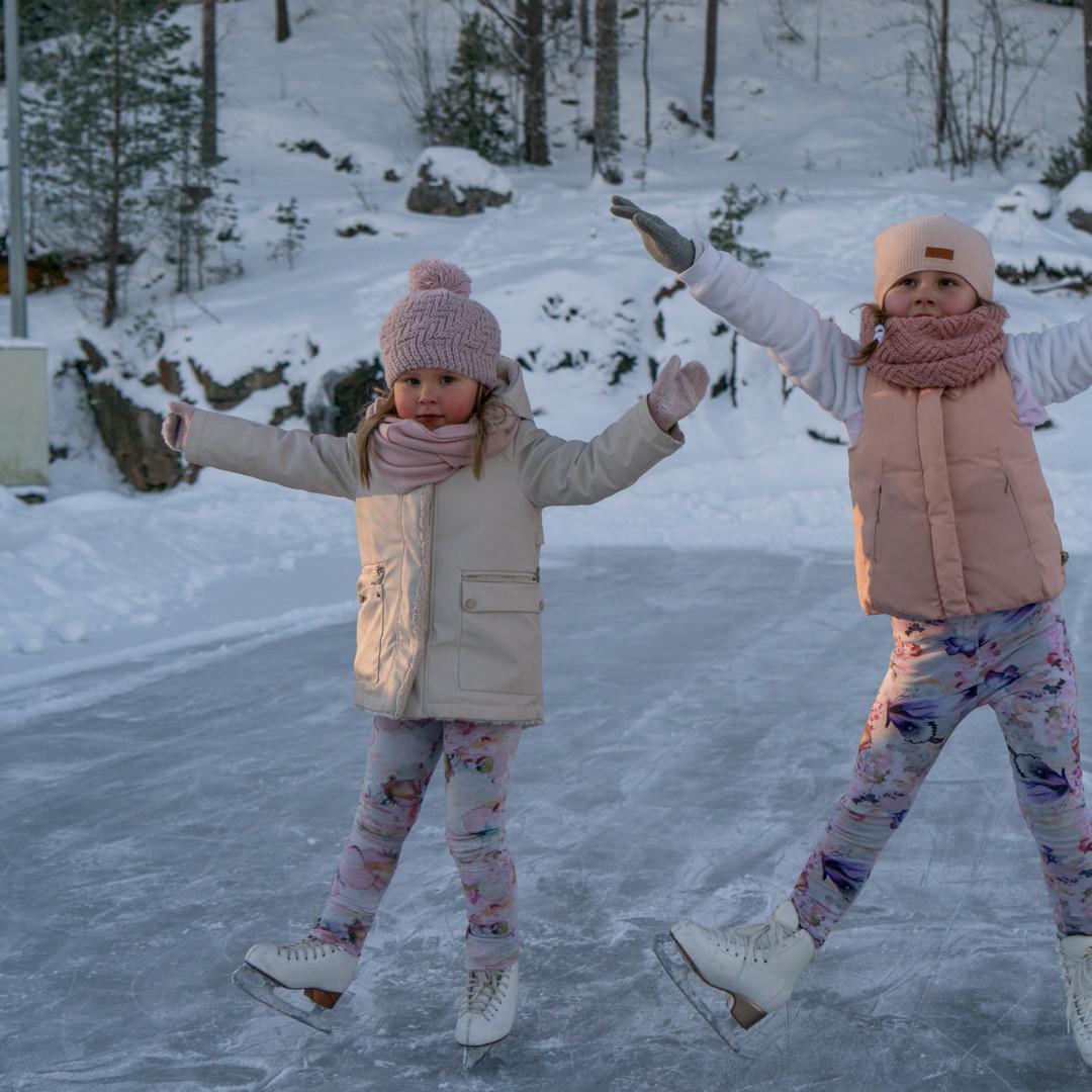 Kaksi pientä tyttöä luistelemassa jäähallin yläkentällä.