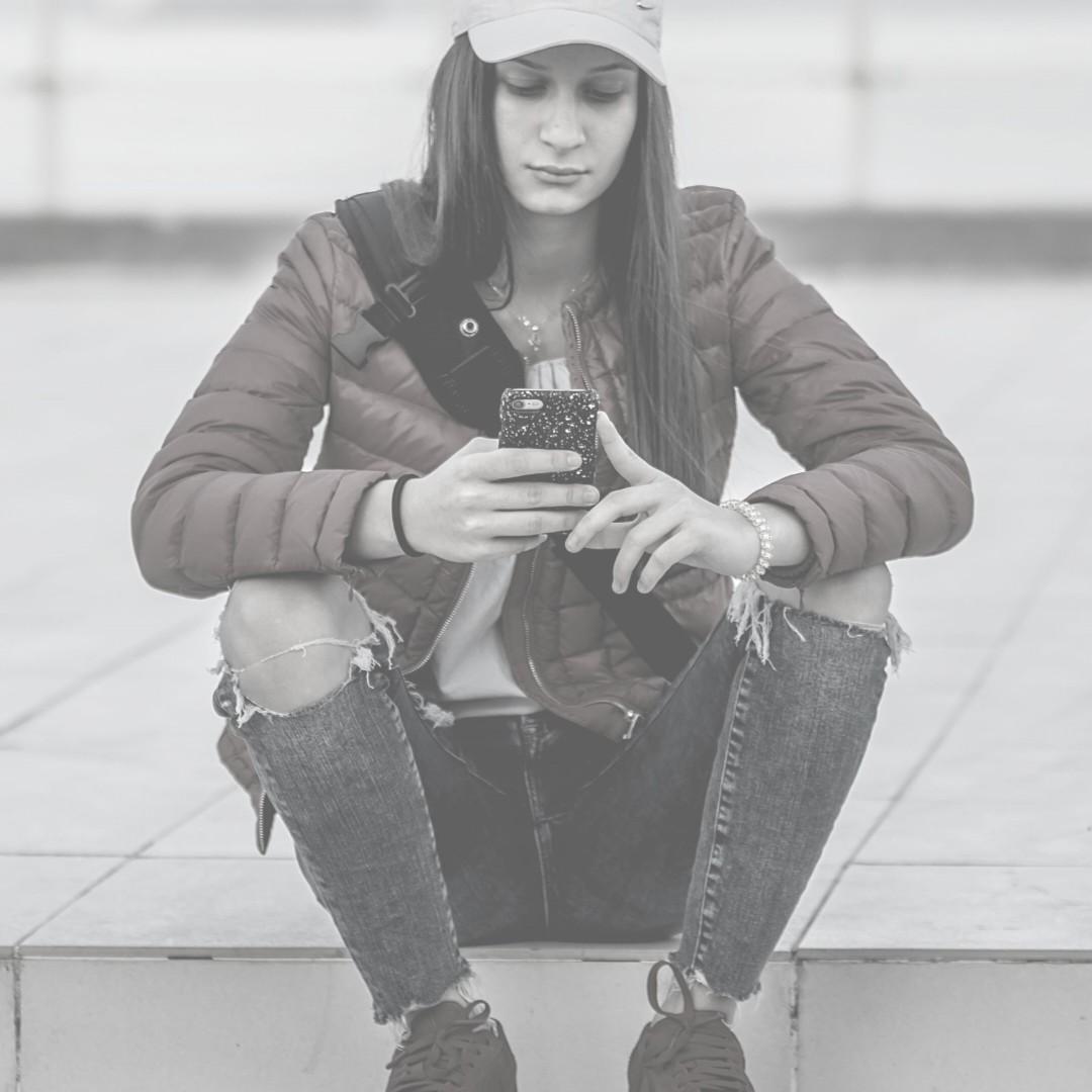Tyttö istuu portailla ja käyttää kännykkää.