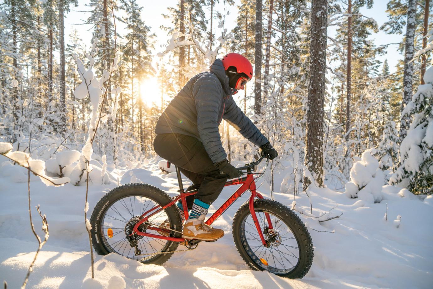 Mies pyöräilee fatbike-pyörällä talvisella Paltanmäellä Orivesi-JonSukat jalassaan.