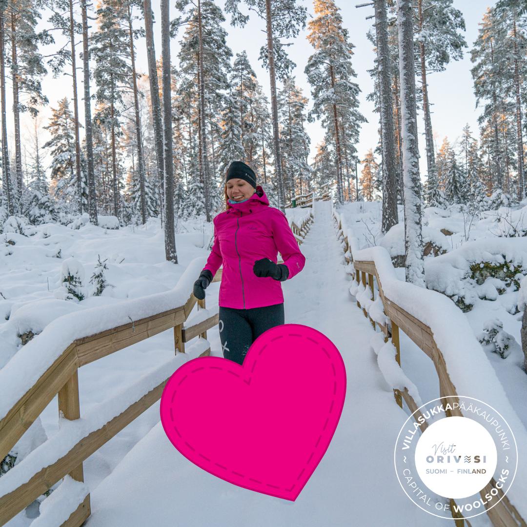 Nainen juoksee lumisilla Paltanmäen elämysportailla. Jalkojen päälle on lisätty pinkki sydän, joka peittää jalat.