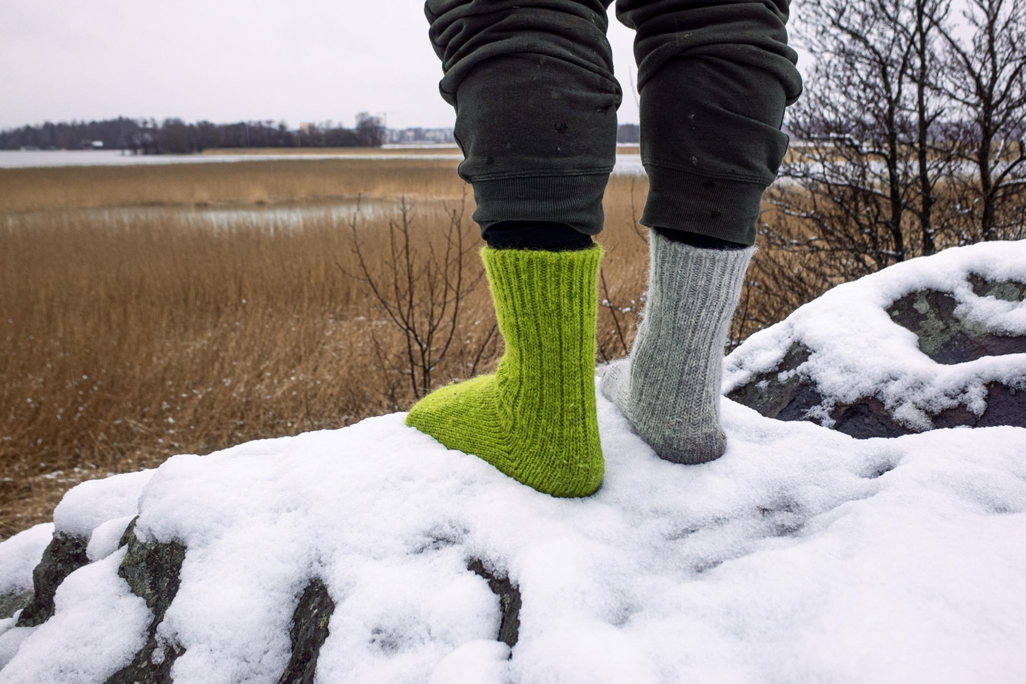 Henkilö seisomassa lumessa eripariset Helsingin Villasukkatehtaan villasukat jalassa.