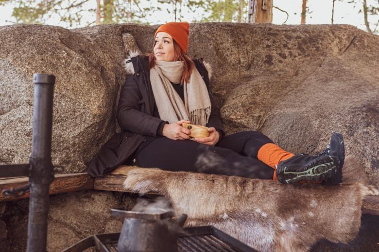 Nainen istuu nuotiolla GreenGo-sukat jalassa.