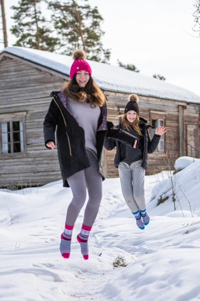 Nainen ja tyttö hyppäävät ilmaan Paltanmäen lumisessa maisemassa pinkit ja turkoosit Orivesi-sukat jalassaan.