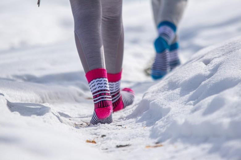 Henkilöiden kävelevät lumella pinkeillä ja turkooseilla Orivesi-sukilla.