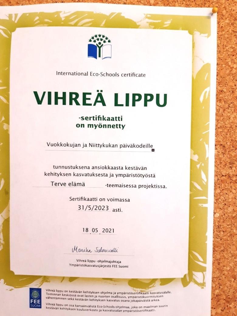 Vihreän lipun sertifikaatti päiväkodin ilmoitustaululla.